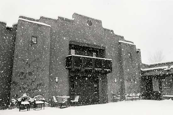 building with heavy snow falling